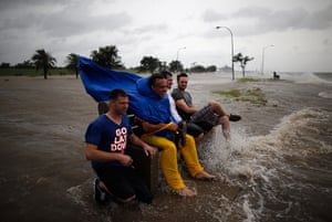 Tropical storm Isaac: A group of men sit on a bench at edge of Lake Pontchatrain in New Orleans