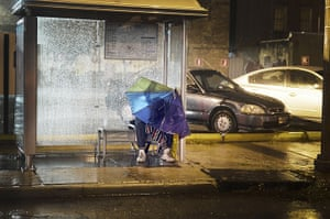 Tropical storm Isaac: A man shelters from the rain at a bus stop in New Orleans