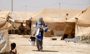A Syrian refugee carries her baby carrying the family washung at Zaatari refugee camp, in Mafraq, Jordan, today.