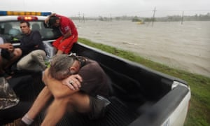 People sit in a rescue truck atop a levee near floodwaters after being rescued in Plaquemines Parish near New Orleans.