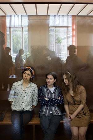 Pussy Riots: Pussy Riot members  sit in a glass cage at a court room