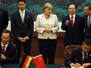Chinese Premier Wen Jiabao, second from right, chats with German Chancellor Angela Merkel, center, during a signing ceremony at the Great Hall of the People in Beijing, China, Thursday, Aug. 30, 2012.