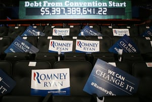 Republican convention: Campaign signs sit on seats in front of a US national debt clock acrued