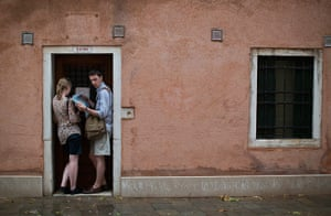 Venice architecture: A couple shelter from the rain as they study their maps of the biennale