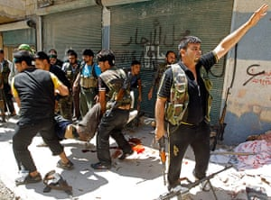 Aleppo: A Free Syrian Army fighter gestures as others carry an injured fighter