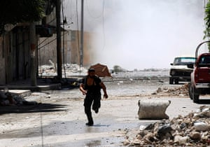 Aleppo: A man runs for cover during clashes in Syria