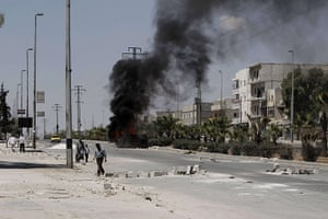 Aleppo: Syrians walk past a burning vehicle in t