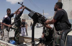Aleppo: Syrian rebel fighters stand around an anti-aircraft machinegun