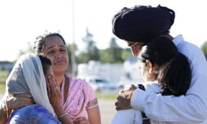 Mourners cry outside the scene of a mass shooting in Oak Creek, Wisconsin