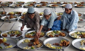 Boys prepare food at a Pakistan mosque before sunset, when Muslims observing Ramadan break the fast