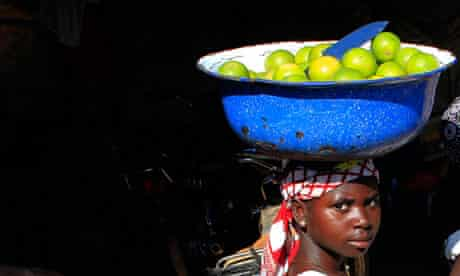 A woman balances a container of oranges for sale on her head in a village near Abuja