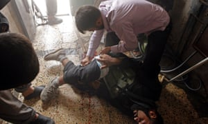 A Free Syrian Army fighter screams in pain after he was injured in a leg by shrapnel from a shell fired from a Syrian Army tank in the Salaheddine district of Aleppo. Photograph: Reuters/Goran Tomasevic