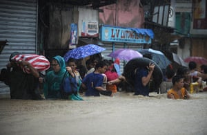 Floods in Manila: Residents wade through a flooded street