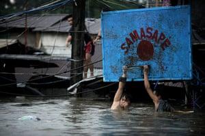 Floods in Manila: Two men hang onto a basketball hoop