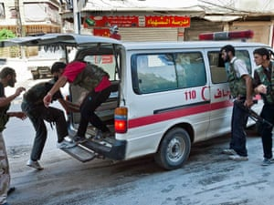 Syrian rebel fighters load a wounded person into an ambulance during clashes with Syrian government forces in the al-Sahkur district of Aleppo. Photograph: Vedat Xhymshiti/AFP/GettyImages