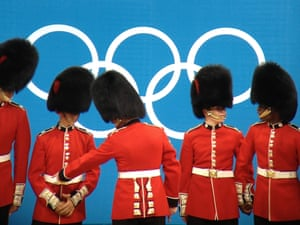 Soldiers wearing busbys pose in front of the Olympic rings at the close of the weightlifting at ExCel tonight.