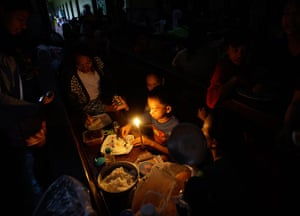 Floods in Manila: An evacuee takes his dinner under candelight