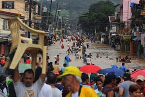 Floods in Manila: Filipinos walk in floodwaters on a main road of Marikina City