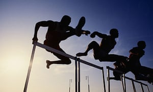 Three men leaping over hurdles seen from below in silhouette