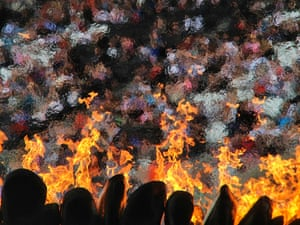 the crowd seen through the Olympic flame in the sunshine