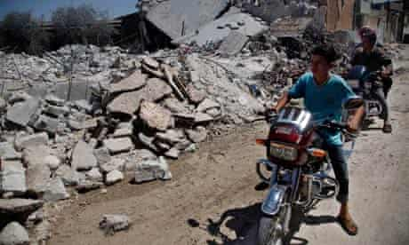 Young men on motorbikes survey damage purportedly caused by air strikes in the outskirst of Aleppo