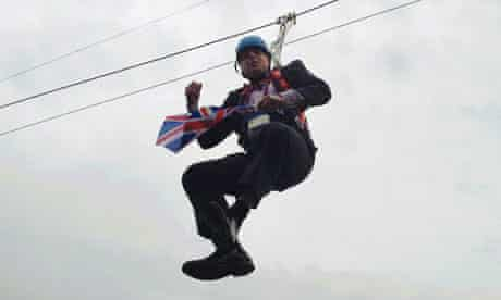 London Mayor Boris Johnson dangles in the air after getting stranded on a zip wire at Victoria Park