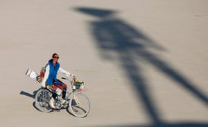 Burning Man: A participant rides past the shadow of the Man during the Burning Man 2012