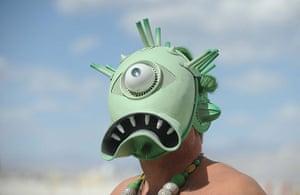Burning Man: A man with a creature mask walks the playa at Burning Man 2012