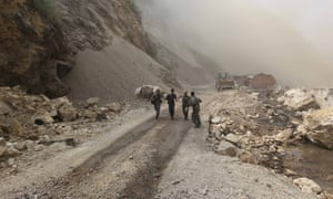 Rescuers run across the landslide-hit section of a mountain road on September 9, in Yiliang County, China. At least 81 people were killed and 821 others injured after two earthquakes jolted the border of Yunnan and Guizhou provinces on Friday.
