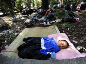 A child sleeps near rescue workers at a makeshift emergency relief center in Yiliang, after the earthquakes rocked southwestern Guizhou and Yunan provinces last week.