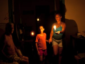 People walk at home uising candles for light during the blackout in Havana, Cuba. Power failed across a large swath of western Cuba plunging millions of people into darkness.