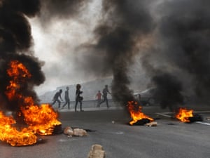 Palestinians walk past burning tyres during a protest against high living costs near the West Bank city of Ramallah. A general strike was declared in the West Bank on Monday.