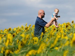 A father and his child play among blooming sunflowers at the Clear Meadow Farm in Jarrettsville, near Baltimore, US