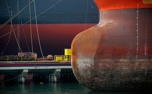 24 hours: Singapore: A worker is dwarfed by vessels berthed at a pier