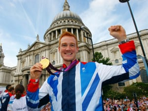 Greg Rutherford holds up his long jump gold medal in front of St Paul's Cathedral