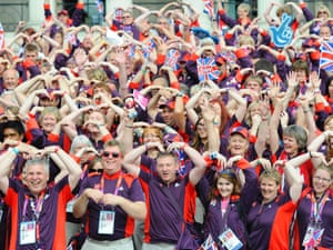 Olympic volunteers pose doing the Mobot in front of the National Gallery before the victory parade of the British athletes of the Olympics and Paralympics Games passing by Trafalgar Square in London