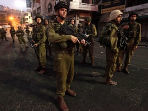 Israeli soldiers out on patrol at first light in the divided West Bank city of Hebron during protests over the rising economic costs.