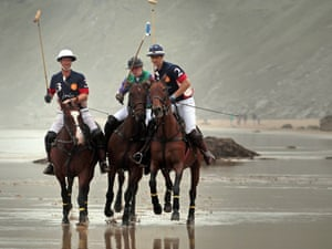 Polo players Rob Brockett on his horse Pachu, Andy Burgess on Shriva and Major Ben Marshall on Burris practise on the beach ahead of tomorrow's beach polo event in Newquay, England.