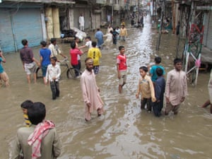 Pakistani youth gather in a flooded street after torrential rain in Sukkur.  At least 78 people have died and dozens more injured in torrential rains and flash floods that have wreaked havoc over the past three days.