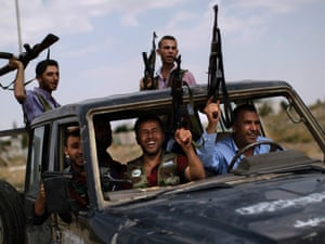 Syrian rebel fighters raise their weapons as they head to fight government forces in Aleppo, Syria.