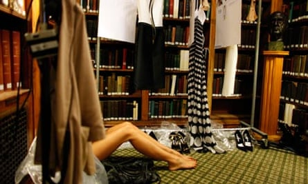 A model takes a break backstage during a fashion show