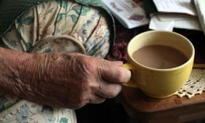 Elderly hands hold a cup of tea