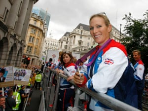 A Royal on a bus! Three day eventer Zara Phillips holds her silver medal as she takes part in the parade.