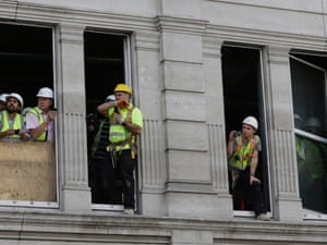 Workers take a tea-break to watch the parade.