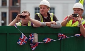 Workmen take pictures as the floats pass by.