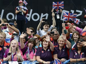 Gamesmakers wave to the athletes on the Mall.