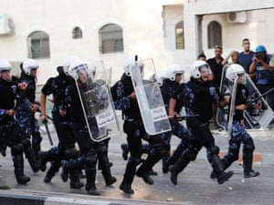 Palestinian police officers charge towards protesters during clashes at a demonstration against high living costs and the government in the West Bank city of Hebron September 10.