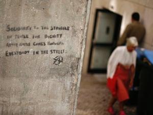 People pass near graffiti in Lisbon September 10, 2012
