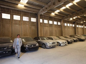ODDY's manager Dimitris Kouvaris walks by confiscated luxury cars inside a warehouse of the Public Property Management Organisation (ODDY), in Athens September 5, 2012.