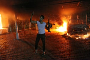 Benghazi protest: An armed man waves his rifle as buildings and cars are engulfed in flames